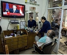 A customer in a Palestinian barber shop in the Old City of Jerusalem watches President Obama's key Mideast speech, June 4, 2009. (AP)